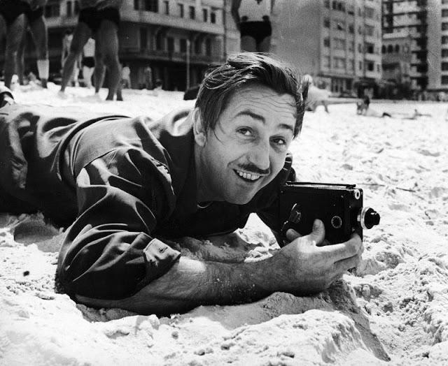 Walt Disney deitado na areia segura uma câmera fotográfica antiga