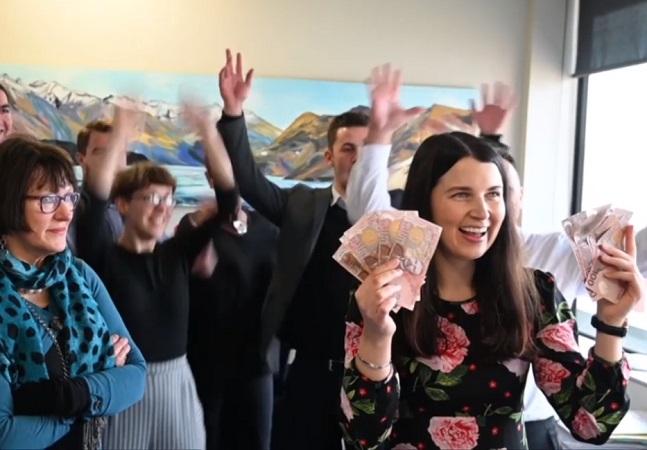 Mulher de cerca de 30 anos sorri enquanto segura diversas notas de dólares neo-zelandeses