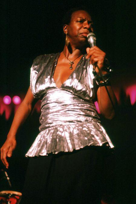 Nina Simone com vestido prateado segura um microfone na mão esquerda