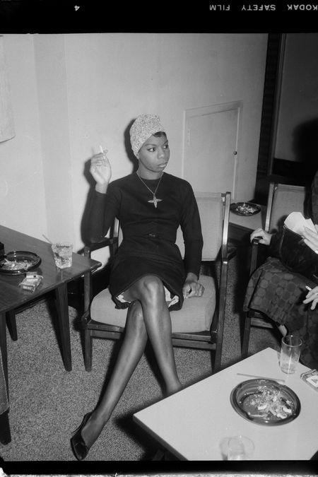Nina Simone sentada de vestido preto e turbante claro fumando um cigarro
