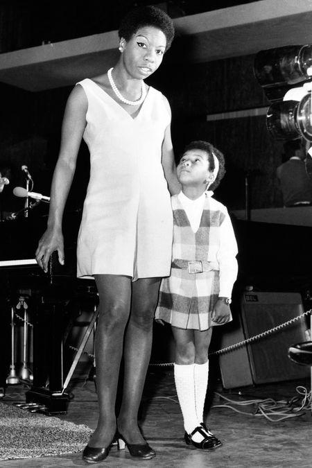 Nina Simone veste um macaquinho branco ao lado de sua filha Lis, de cinco anos, com vestido escolar