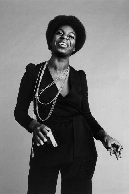 Nina Simone parece dançar feliz com um terno preto e longos colares