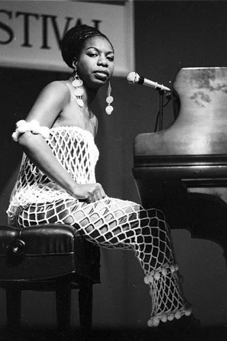 Nina Simone ao piano com um vestido branco vazado