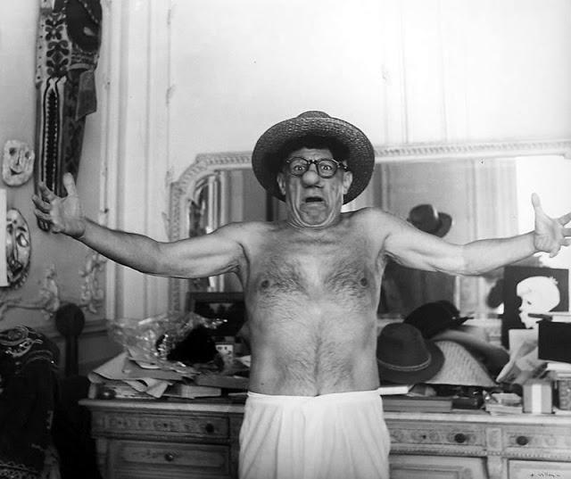 Picasso de bermuda branca, chapéu e braços abertos com uma expressão divertida no rosto