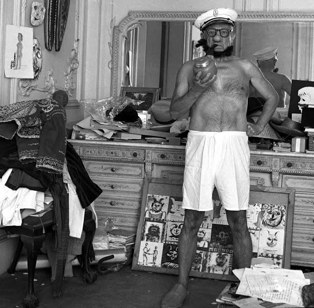 Picasso de bermuda branca, quepe de marinheiro, barba artificial e com um enorme cachimbo na boca