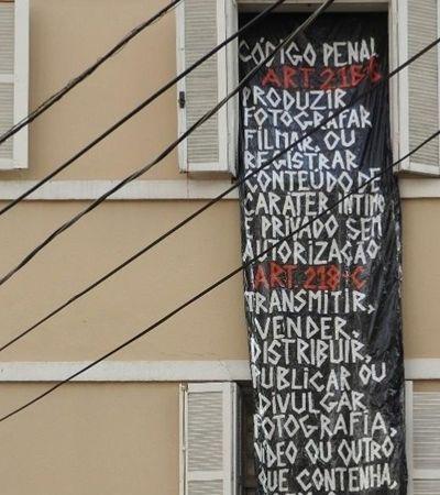 Mulher fotografada nua dentro de casa por vizinhos expõe faixa com o Código Penal