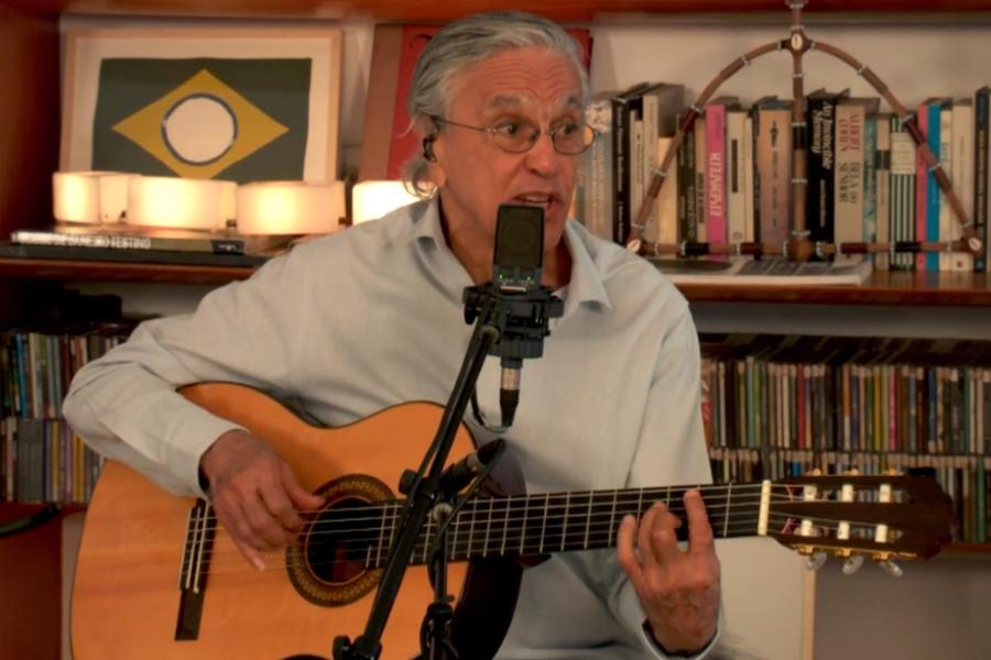 Caetano Veloso sentado com o violão durante live de comemoração ao seu aniversário de 78 anos