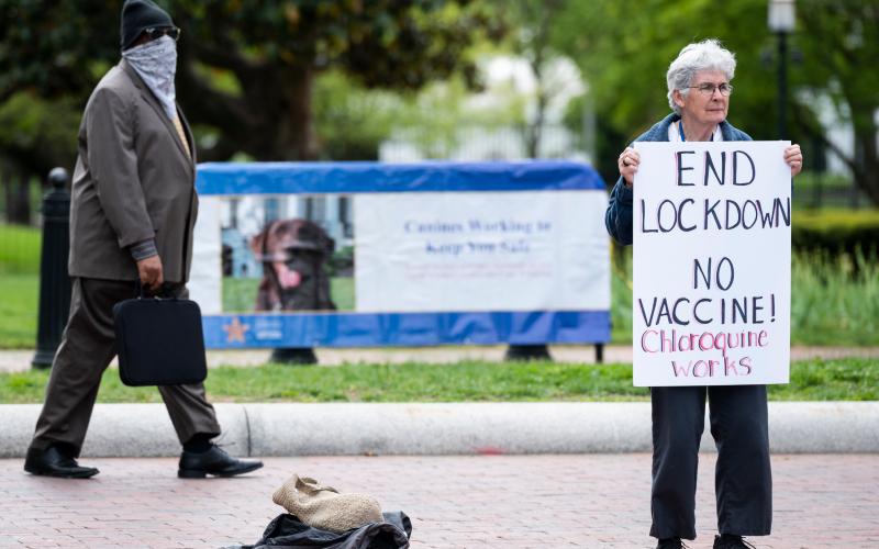 Protestante norte-americana e negacionista segura cartaz contra vacina e a favor da cloroquina