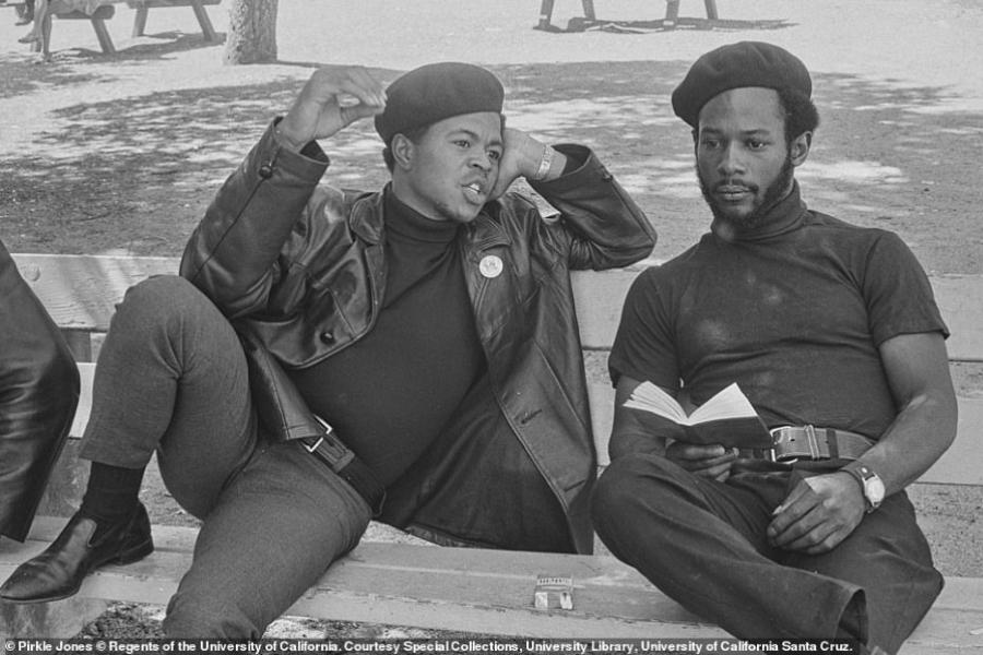 Foto de dois integrantes do Partido dos Panteras Negras conversando no banco do parque