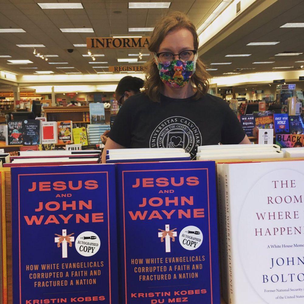 Kristin posa atrás da estante que expõe seu livro em uma livraria.