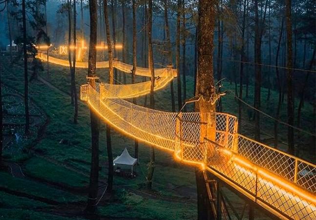 Esta ponte iluminada em floresta da Indonésia parece saída de um sonho