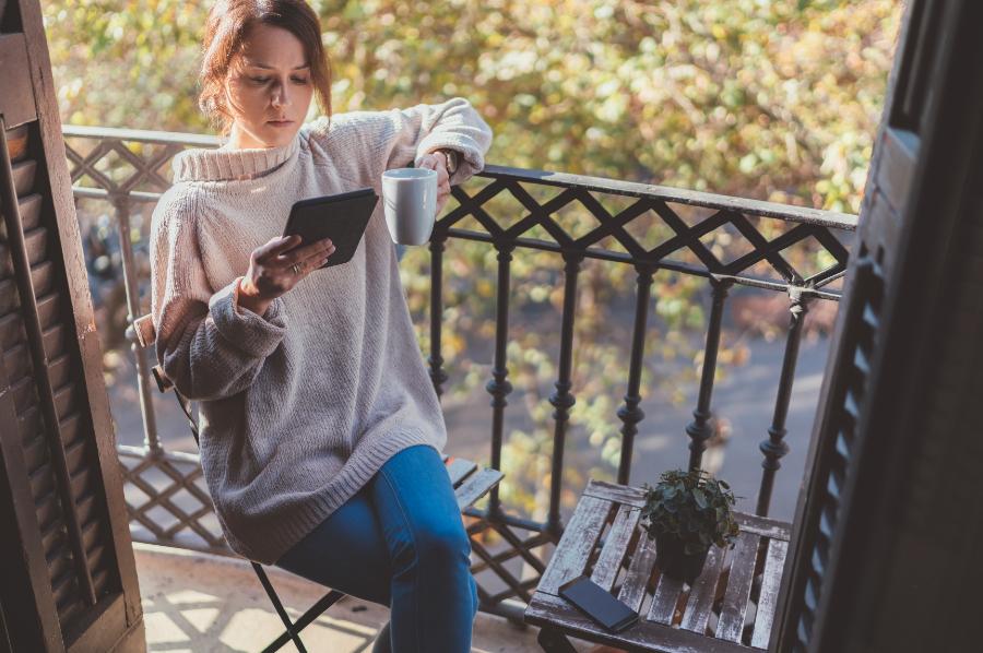 Mulher lendo em um Kindle na varanda
