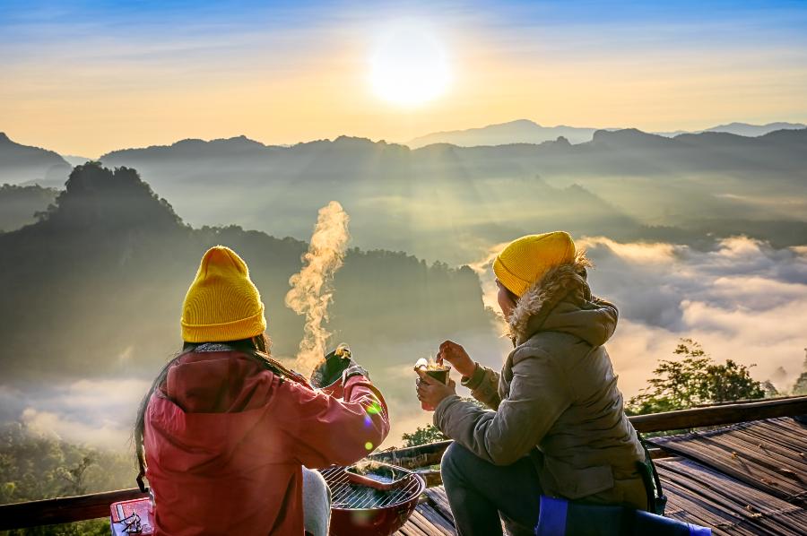 Duas pessoas acampando e olhando o horizonte