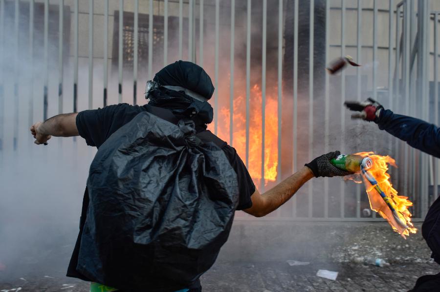 Manifestante se preparando para jogar um coquetel molotov