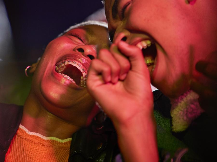 Dois amigos gargalhando muito enquanto estão iluminados por uma luz colorida