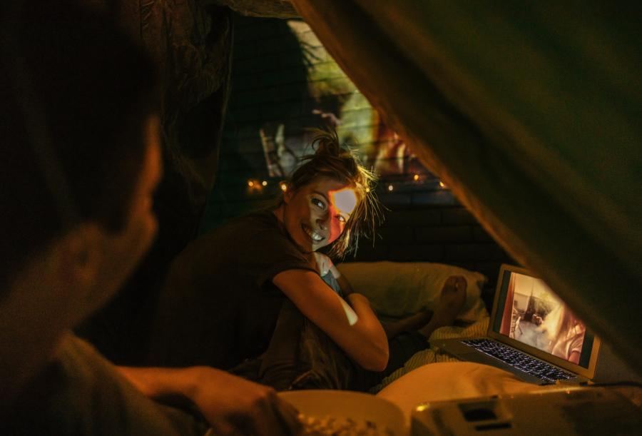 A imagem mostra um casal se entreolhando enquanto assiste a um filme projetado na parede