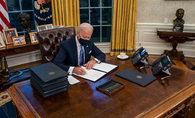 Joe Biden de máscara trabalhando em sua mesa no Salão Oval