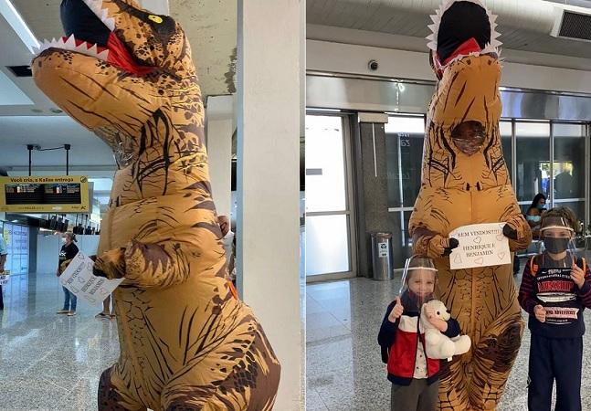 Mãe recebe filhos em aeroporto vestida de dinossauro para se proteger da covid-19