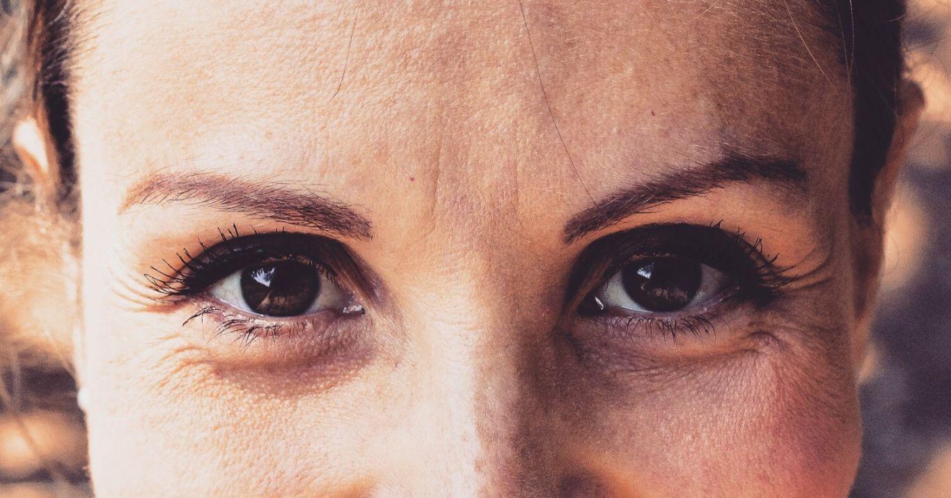 Olhos castanhos de uma mulher que aparenta estar sorrindo