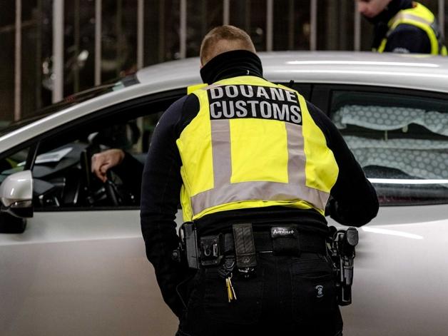 Funcionário da alfândega holandesa inspecionando veículo na entrada do país