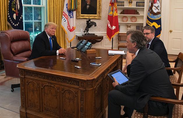 Trump sendo entrevistado com seu botão vermelho de Coca Diet à mesa