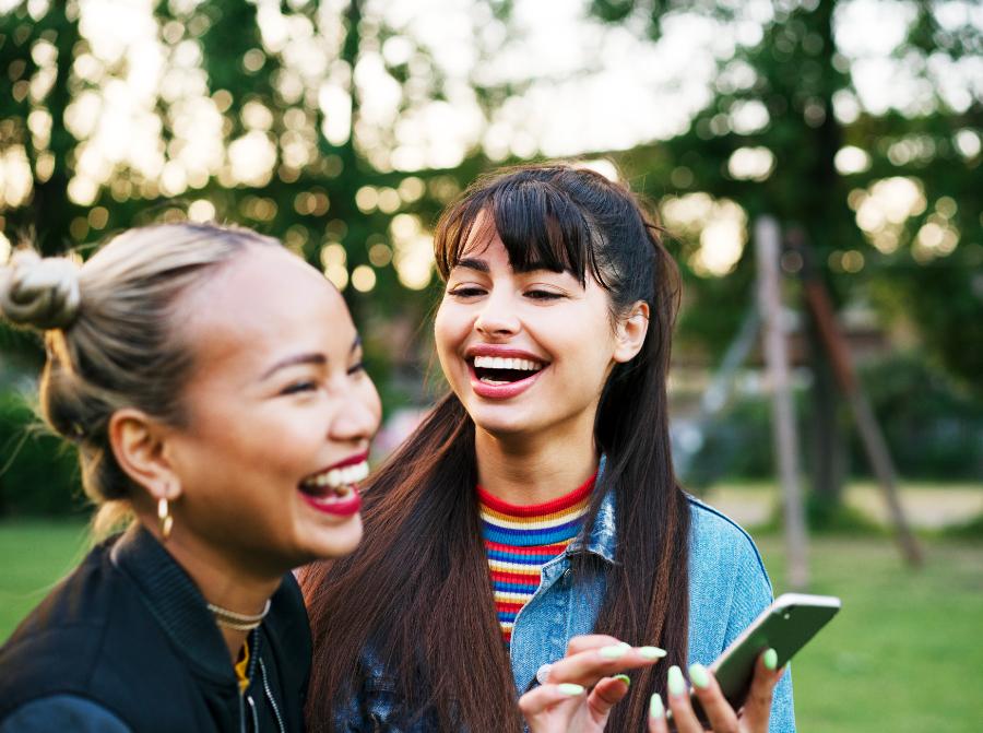 Duas amigas dando risadas em um local gramado