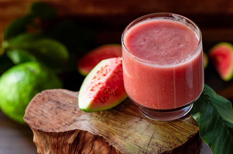 Imagem de suco de goiaba em um copo junto a uma fatia da fruta ao lado