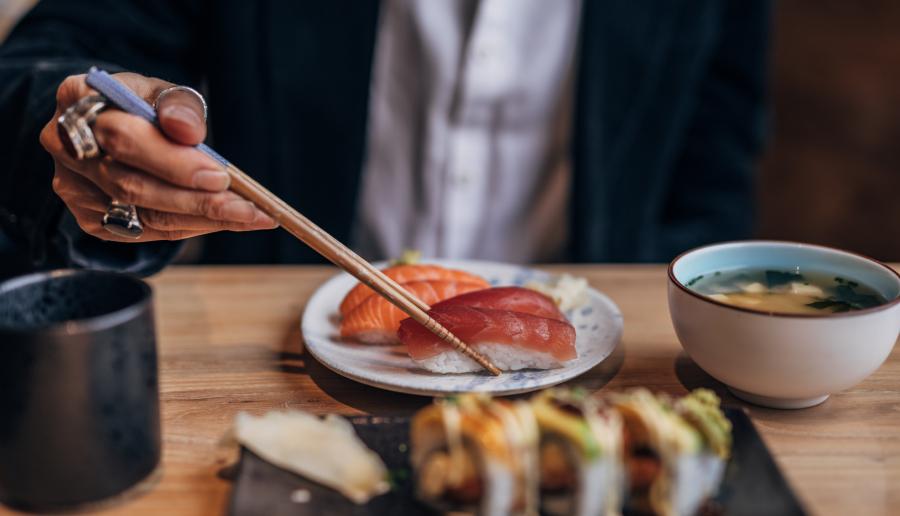 Imagem de uma pessoa comendo uma refeição de origem oriental