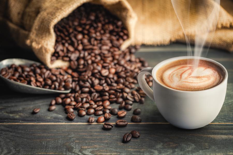 A imagem mostra um saco de grãos de café dispostos sobre uma mesa com uma xícara de café decorado ao lado