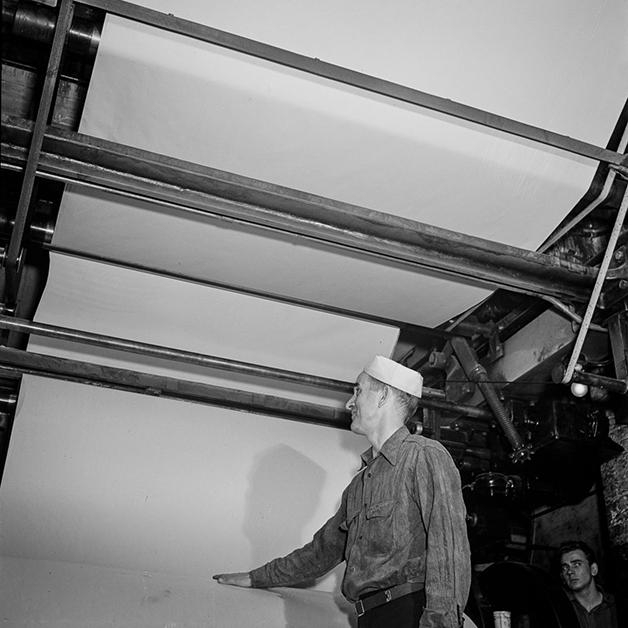 Técnico diante da folha branca em um prensa para rodar o NY Times em 1942, fotografado por Marjory Collins