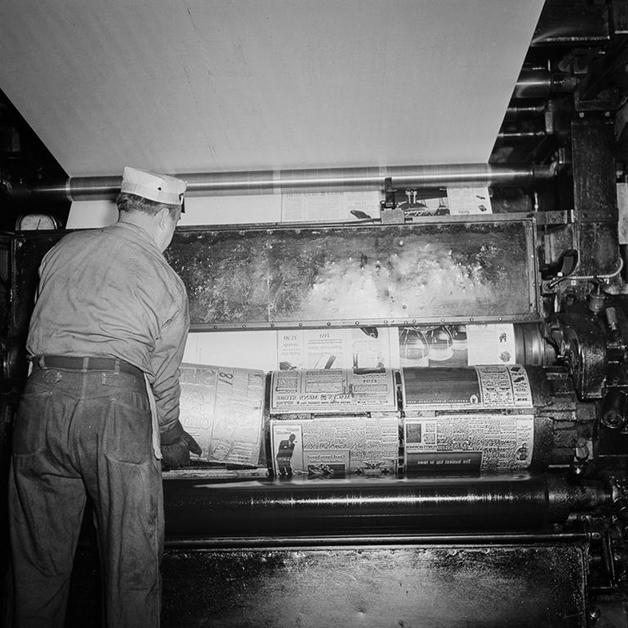 Técnico encaixando as Placas de zinco com as páginas na prensa para rodar o jornal, fotografado por Marjory Collins