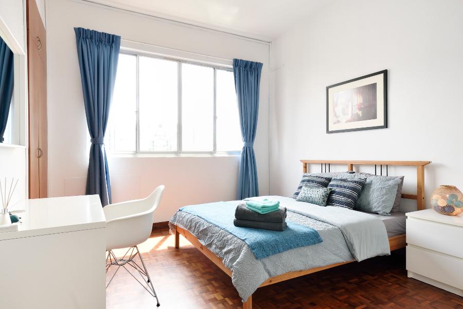 Imagem de um quarto organizado, com a roupa de cama arrumada, limpa e combinando com o ambiente