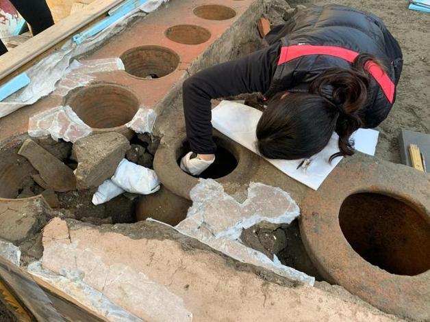 Arqueóloga recolhendo restos de alimentos petrificados em lanchonete descoberta em Pompéia