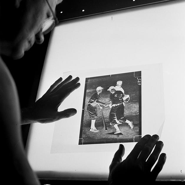 Técnico fotográfico inspecionando o negativo de uma foto antes de passá-la para uma placa de zinco, para a impressão do NY Times em 1942, fotografado por Marjory Collins