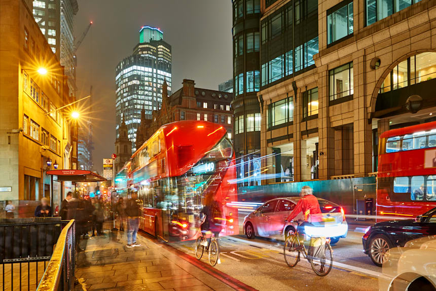 Rua de Londres movimentada pelo trânsito de ônibus, caros e bicicletas