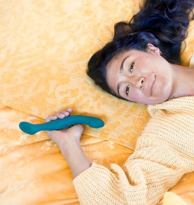 Mulher com vibrador térmico Sway, da marca Lora DiCarlo