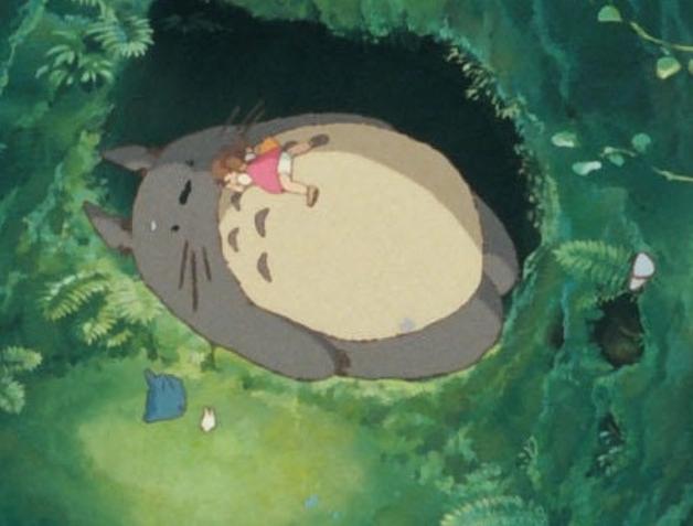 A personagem Mei Kusakabe deitada na barriga de Totoro em cena vista de cima