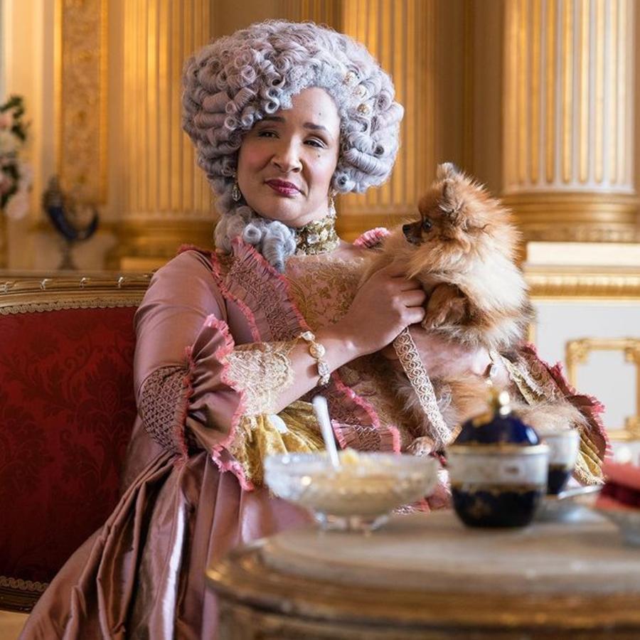 Rainha Charlotte segurando seu cachorrinho de estimação sentada