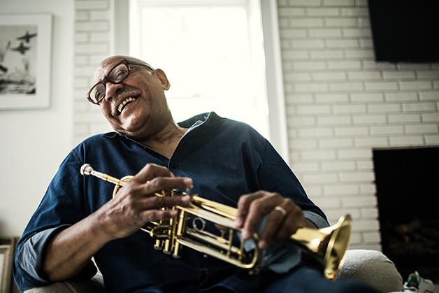 Um senhor rindo com seu trompete