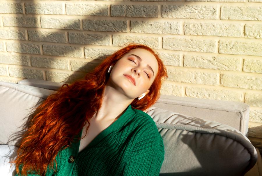 A imagem mostra uma mulher ouvindo algo relaxante com um fone de ouvido bluetooth