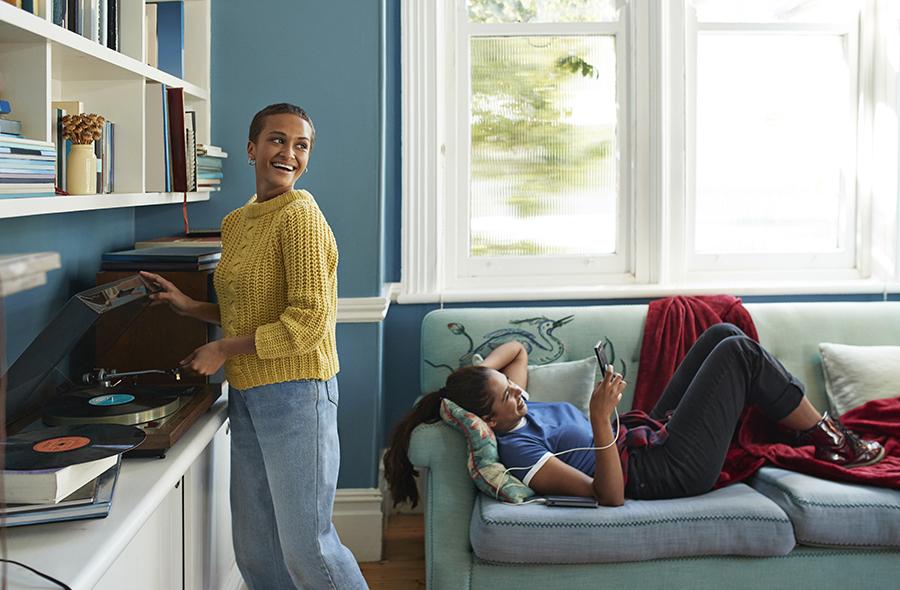 Foto de amigas se divertindo em casa ao som de um disco de vinil tocando em uma vitrola