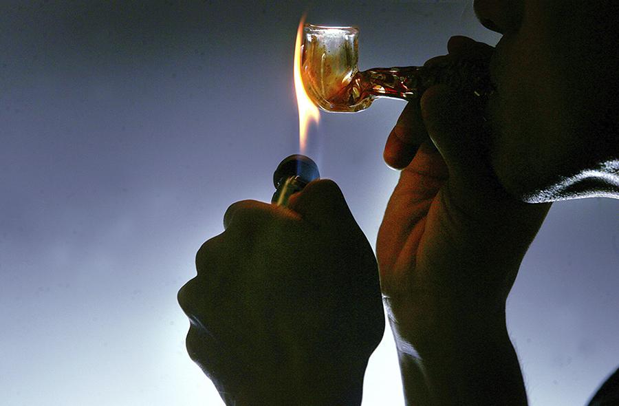 Foto de uma pessoa consumindo droga por meio do fumo