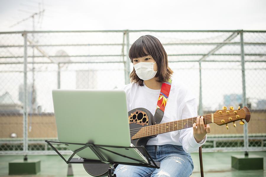 Foto de uma mulher tocando violão enquanto estuda música pelo computador