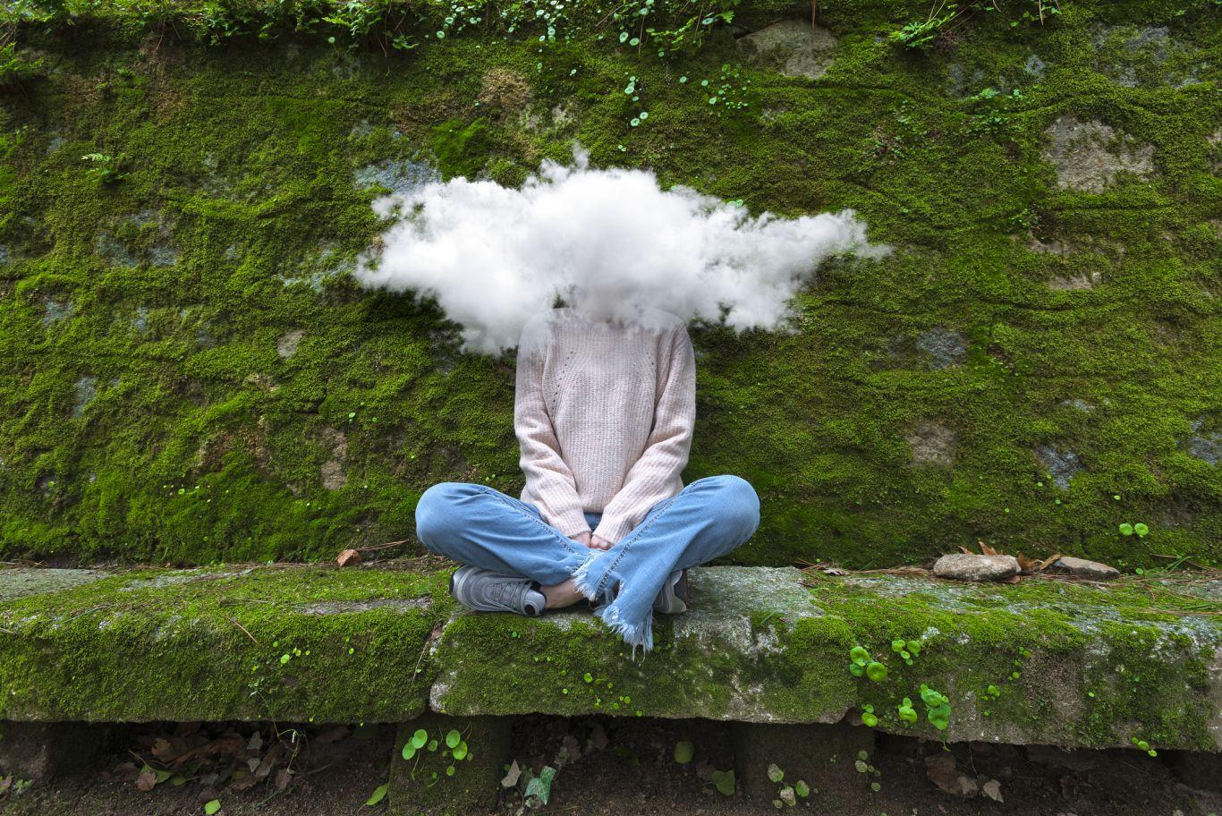 Pessoa sentada com nuvem na cabeça cobrindo o rosto