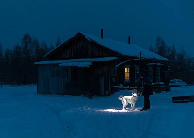 Um morador de Lacútia com seu cachorro no frio da região
