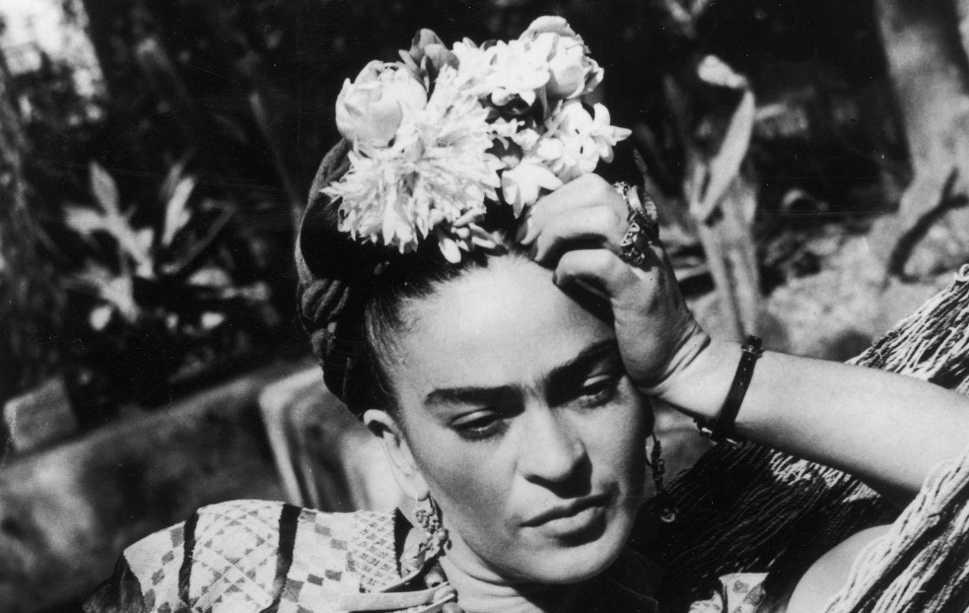 1950: a artista mexicana Frida Kahlo (1907 - 1954), vestindo uma fantasia folclórica e flores no cabelo, apoia a cabeça na mão enquanto está deitada em uma rede. (Foto por Hulton Archive / Getty Images)