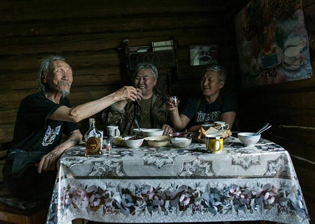Moradores de Lacútia, na Rússia, brindando e bebendo