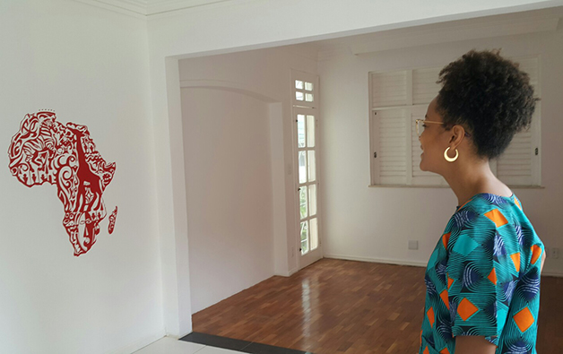 A professora Barbara Carine diante de uma representação do continente africano em uma sala de aula