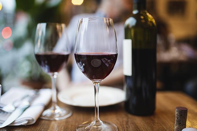 Taças de vinho com garrafa ao fundo