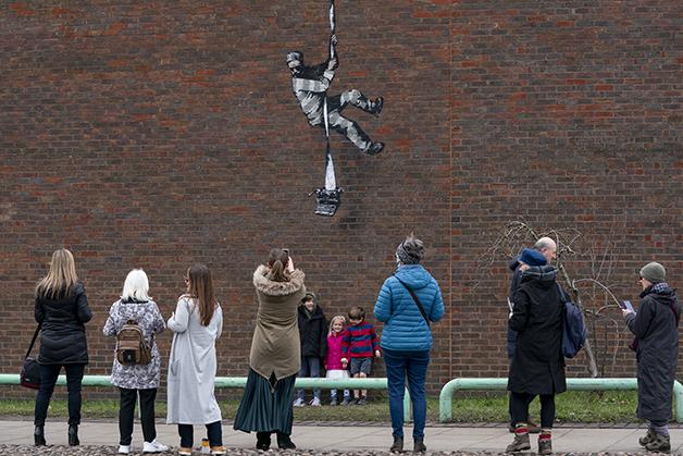 Passantes fotografando a nova obra de Banksy em Reading, na Inglaterra